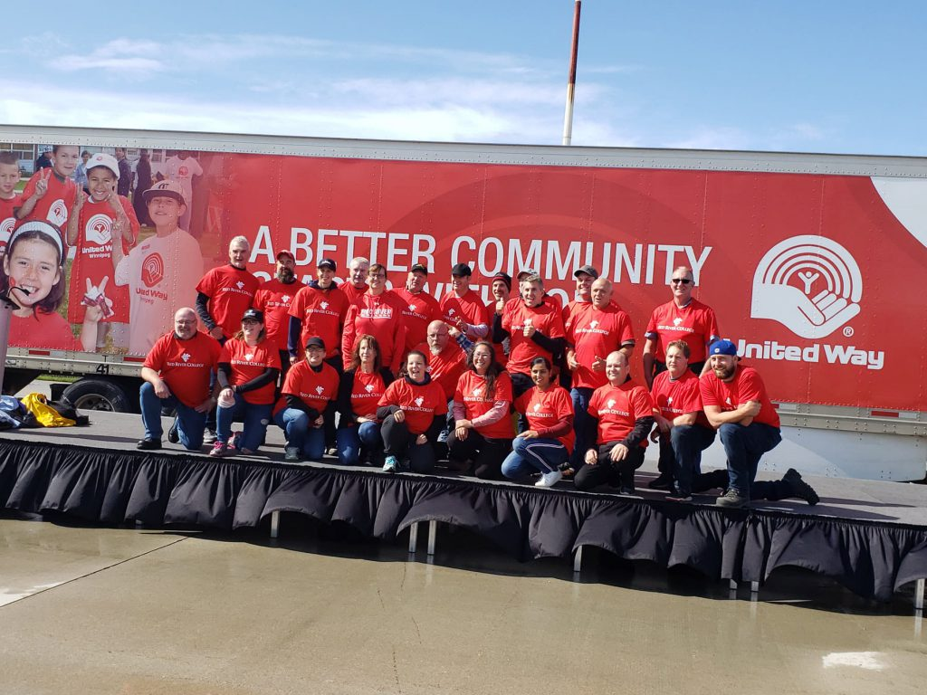 Red River College team sitting in front of United Way banner.