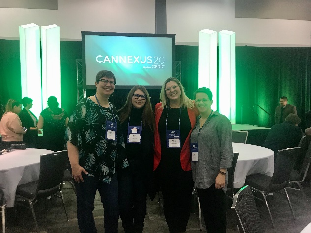 Four Campus Manitoba employees standing in front of Cannexus20 screen.