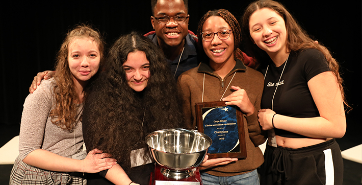 Five USB students holding the Ethics Bowl trophy.