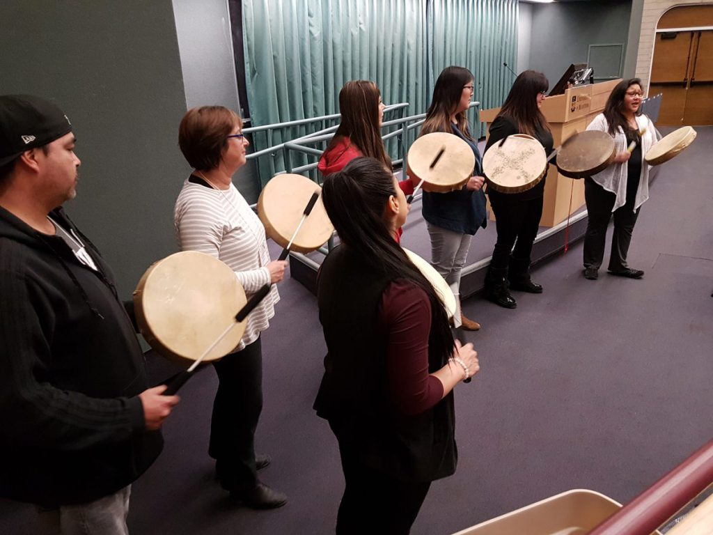 Seven people play the drum for the UM Symposium. Manitoba news in post-secondary.
