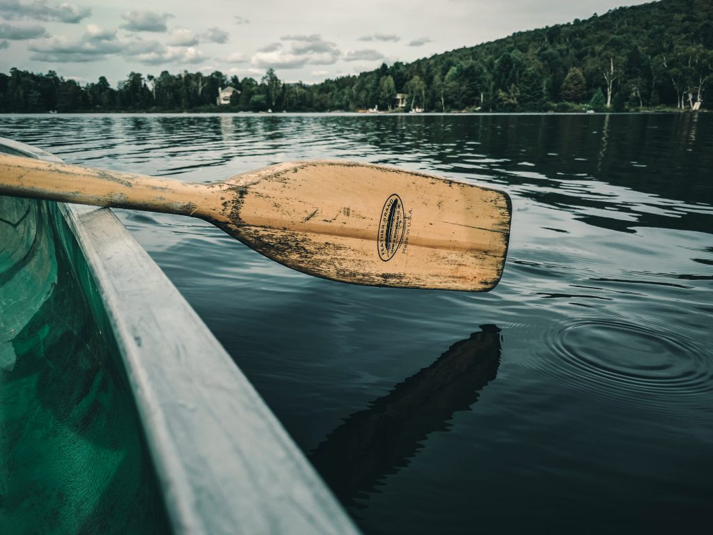 canoe paddle hovering above lake water