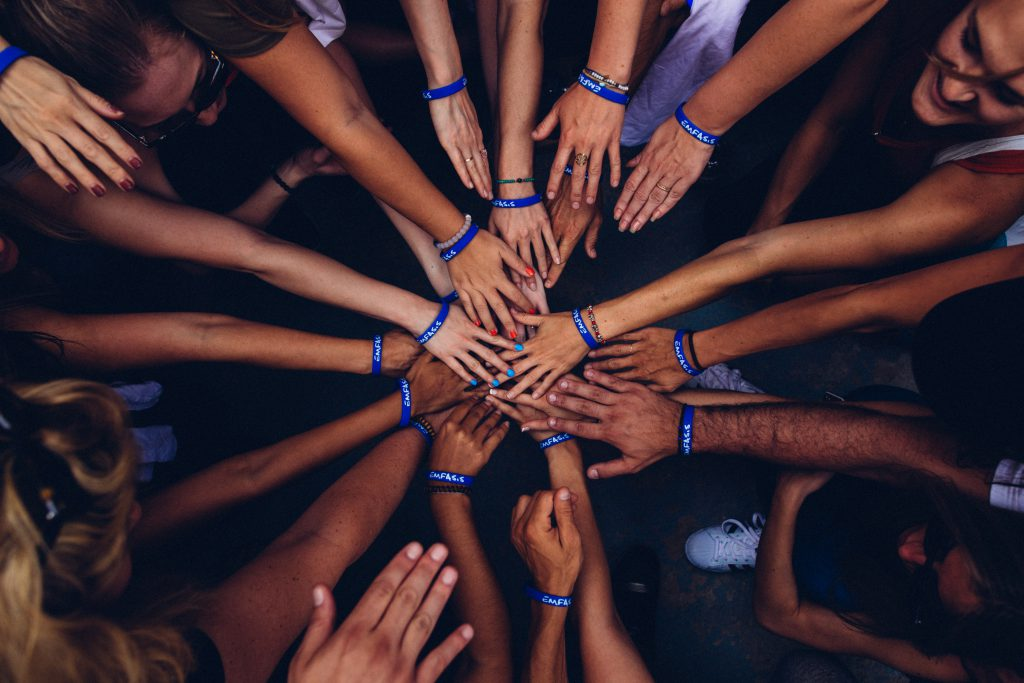 A group of people in a circle with their hands stretched into the middle.